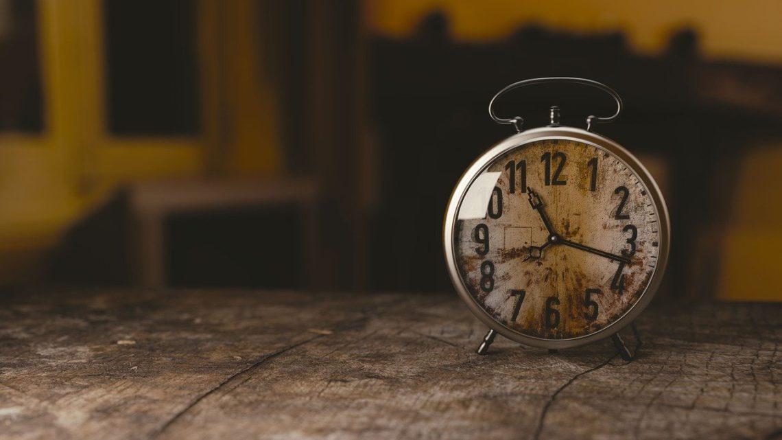 Stary zegar z budzikiem stojący na drewnianym stole