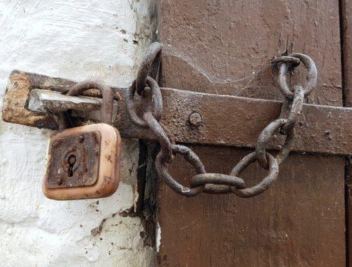 Stare drewniane drzwi zamknięte łańcuchem na kłódkę