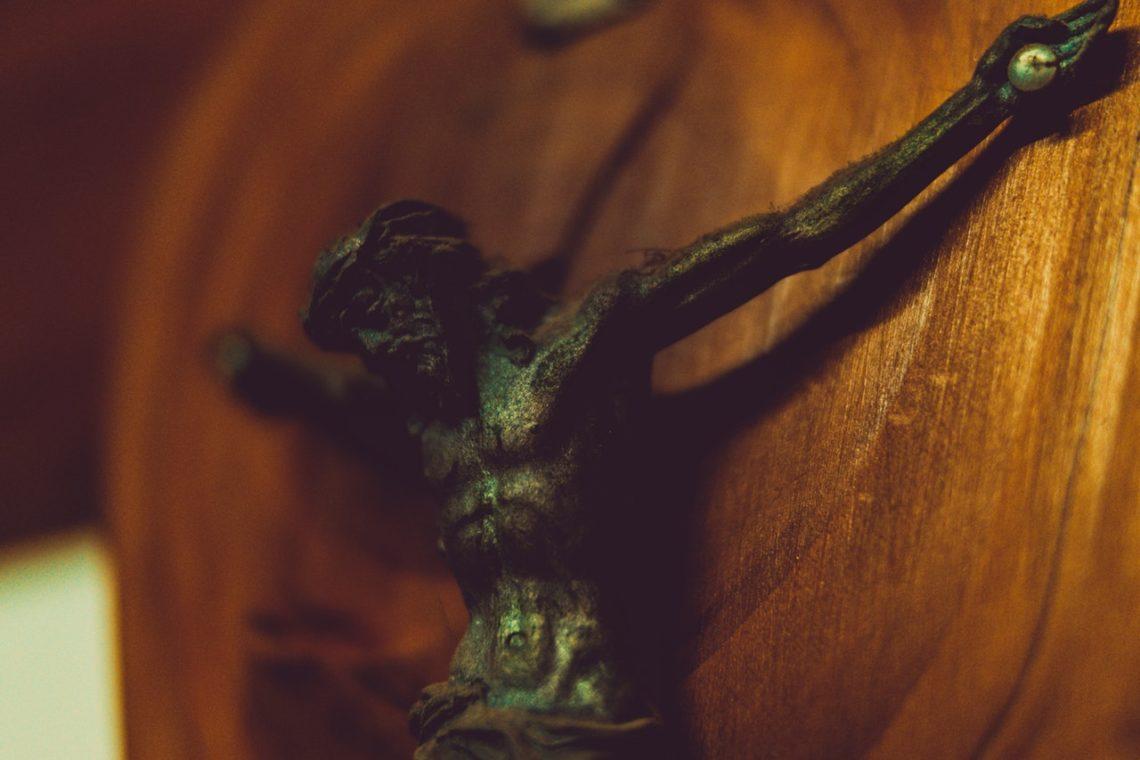 Metalowa figura Jezusa na drewnianej podporze