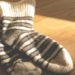 Biało czarne skarpetki z wełny na drewnianej podłodze oświetlone promieniami słońca