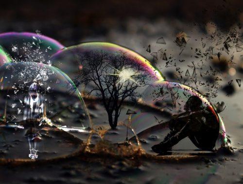 Połówki baniek mydlanych na ziemi, w jednej z nich miniaturka drzewa, w drugiej siedzący załamany człowiek