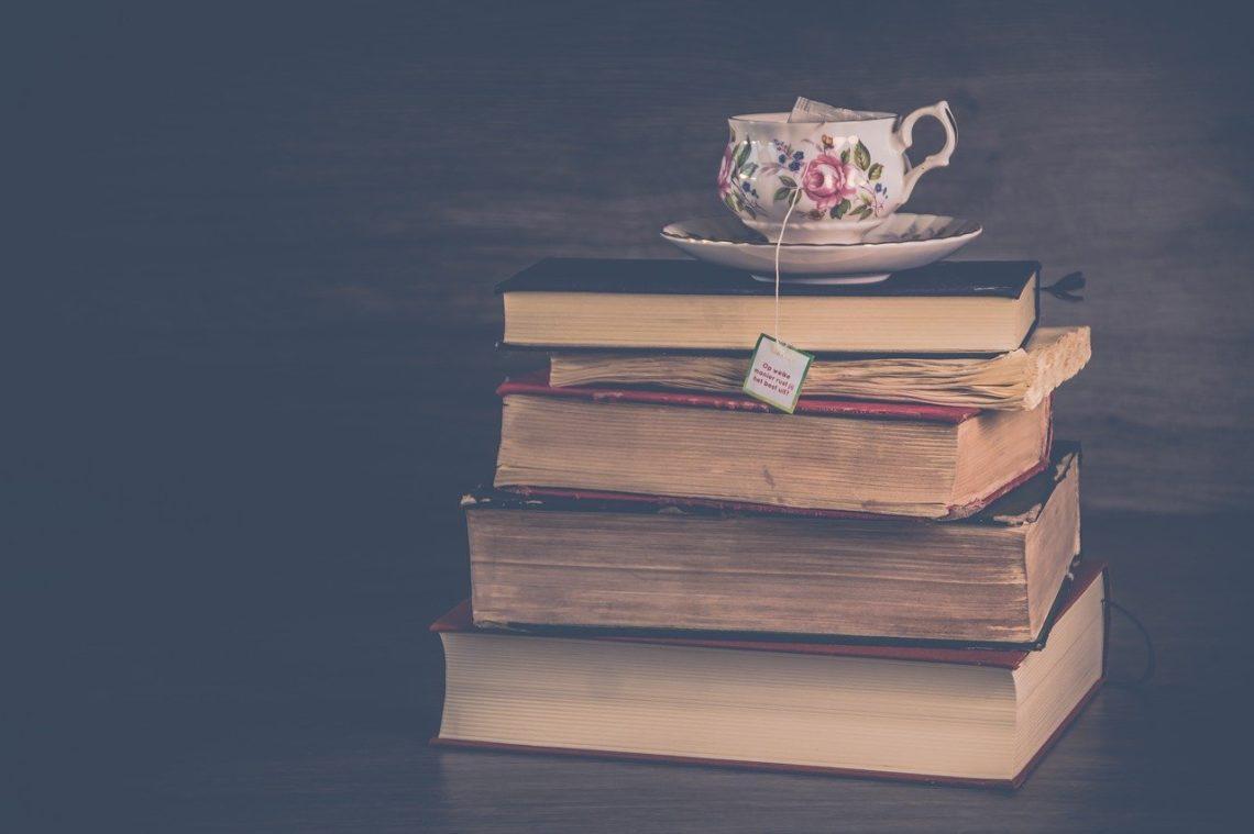 mama i relaks - piramida z książek a na szczycie szklanka z herbatą