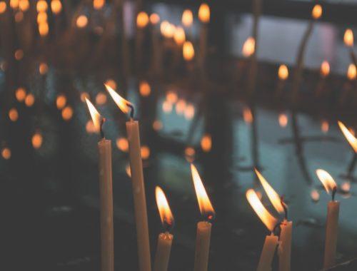 Cienkie zapalone świece będące synonimem światła i miłosierdzia Boga