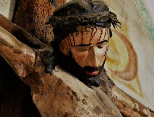 Jezus miłosierny zakrwawiony na drewnianym krzyżu, za nim majaczy fresk świątyni.